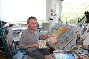 Island-based wildlife artist Jeremy Paul in his studio with the 'Big Cats' stamps due for release on September 13